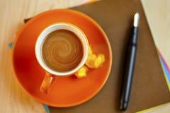 在棕色写信纸的橙色咖啡杯与笔 库存图片