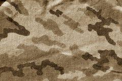 在棕色口气的肮脏的伪装布料 免版税图库摄影