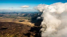 在棕色和绿色领域上云彩的空中射击  免版税库存图片