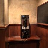 在棕色墙壁上的公用电话 免版税库存照片