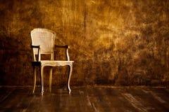 在棕色墙壁背景的老椅子 免版税库存图片