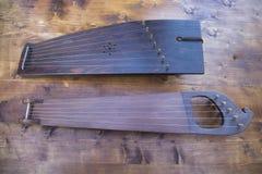 在棕色委员会桌上的木古代弦乐器  免版税图库摄影
