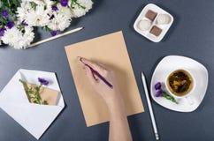 在棕色工艺纸一张的女性手文字  新chrys 库存照片
