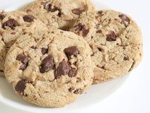 在棕色布料背景的巧克力曲奇饼 巧克力曲奇饼在白色板材,特写镜头射击了 库存图片