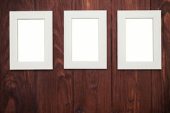 在棕色木书桌上的三个垂直的框架 免版税库存图片