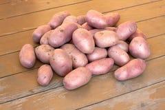 在棕色木地板关闭的成熟红色土豆 图库摄影