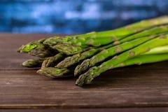 在棕色木头的新鲜的绿色芦笋矛 免版税库存图片
