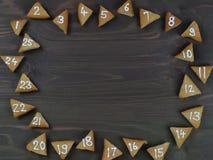 在棕色木头的25个被编号的出现曲奇饼 库存照片