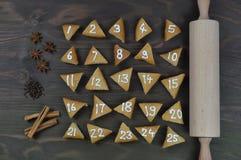 在棕色木头的25个被编号的出现曲奇饼 免版税库存照片