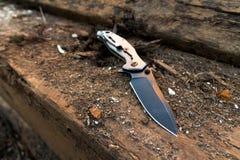 在棕色木头背景的作战刀子  免版税库存图片