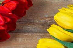 在棕色木板的黄色和红色郁金香 背景,样式,纹理 库存图片