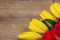 在棕色木板的黄色和红色郁金香 背景,样式,纹理 免版税库存图片