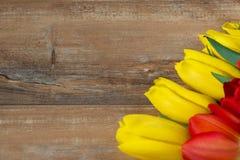 在棕色木板的黄色和红色郁金香 背景,样式,纹理 图库摄影