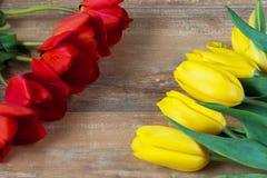 在棕色木板的黄色和红色郁金香 背景,样式,纹理 免版税库存照片