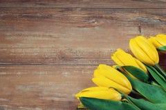 在棕色木板的黄色郁金香 背景,样式,纹理 免版税库存照片