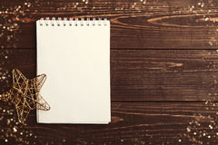 在棕色木桌上的圣诞节空白的笔记本 免版税库存照片