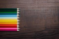 在棕色桌背景的多彩多姿的铅笔 库存照片