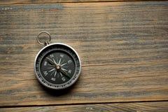 在棕色木桌背景的指南针 免版税库存图片