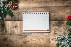 在棕色木桌背景的白纸笔记本 顶视图 免版税库存图片