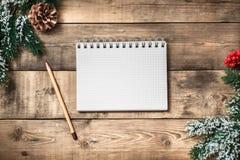 在棕色木桌背景的白纸笔记本 顶视图 免版税库存照片