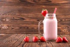 在棕色木背景的一个桃红色饮料 在金属螺盖玻璃瓶和新鲜的草莓的一名乳脂状的圆滑的人 自创鲜美奶昔 免版税库存图片
