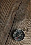在棕色木背景的指南针 库存图片
