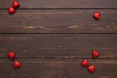 在棕色木背景的红色心脏 库存照片