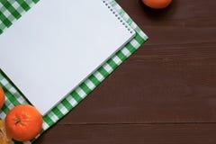 在棕色木背景的食谱笔记本,顶视图 图库摄影