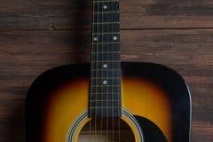 在棕色木背景的黄色音响木吉他 库存照片