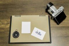 在棕色板料的空白的小白皮书与照相机和指南针 库存图片