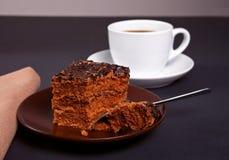在棕色板材的可口巧克力蛋糕有咖啡的在黑桌上的 免版税图库摄影