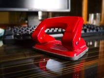 在棕色桌上的红色打孔器 库存照片