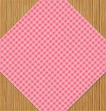 在棕色橡木木表上的桃红色方格的桌布 免版税库存照片