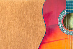 在棕色沙发背景的声学吉他 库存照片