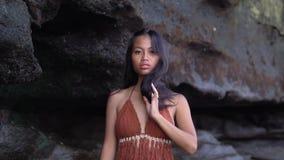 在棕色泳装的很好的亭亭玉立的东方模型在黑岩石下,照相机的姿势 股票视频