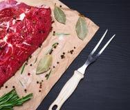 在棕色牛皮纸的牛里脊肉和厨房分叉 库存照片