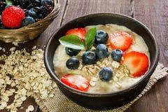 在棕色瓦器碗的燕麦粥粥用成熟莓果 健康的早餐 图库摄影