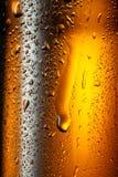 在棕色瓶的水下落啤酒。 免版税库存照片