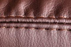 在棕色皮革材料的针螺纹作为背景 库存图片