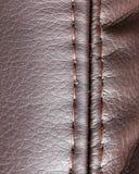 在棕色皮革材料的针螺纹作为背景 免版税库存照片