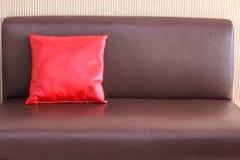 在棕色皮革沙发的一个红色枕头 免版税库存照片