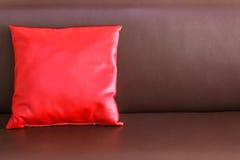 在棕色皮革沙发的一个红色枕头 免版税图库摄影