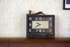 在棕色皮革沙发的葡萄酒时钟 库存照片