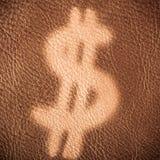 在棕色皮革背景的美元的符号 概念性经济财务图象货币健康 免版税图库摄影