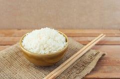 在棕色碗的白米有木筷子的 库存照片