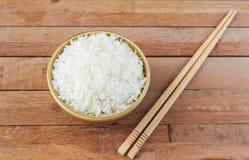 在棕色碗的白米有木筷子的 免版税库存图片