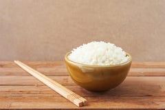在棕色碗的白米有木筷子的 库存图片