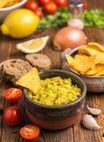 在棕色碗的鳄梨调味酱捣碎的鳄梨酱有在自然木d的玉米片的 图库摄影