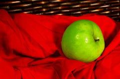 在棕色篮子的绿色苹果与红色织品 免版税库存照片