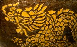 在棕色背景的卷起的龙金子 免版税库存图片